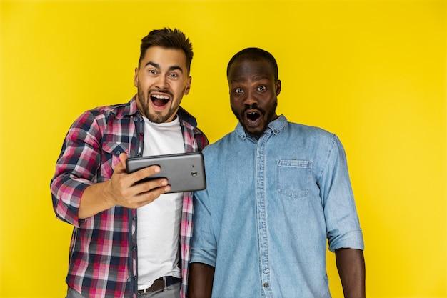 Gelukkig afgevraagd europese en afro-amerikaanse man in informele shirts Gratis Foto