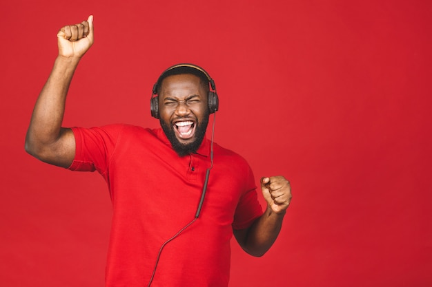 Gelukkig afro-amerikaanse dansende man genieten van lied uit de koptelefoon Premium Foto