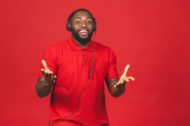 Gelukkig afro-amerikaanse dansende man genieten van lied uit koptelefoon geïsoleerd op rode achtergrond. Premium Foto