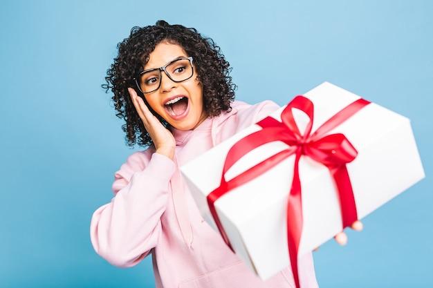 Gelukkig afro-amerikaanse krullende dame in casual lachen terwijl huidige geschenkdoos geïsoleerd op blauwe achtergrond. Premium Foto