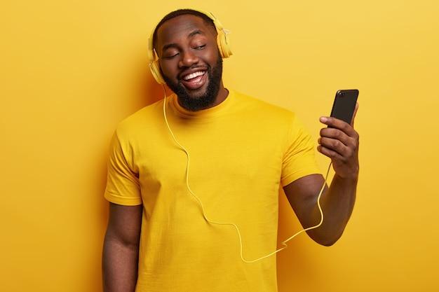 Gelukkig afro-amerikaanse man geniet van lied om mee te zingen, houdt moderne mobiele telefoon aangesloten op een koptelefoon Gratis Foto