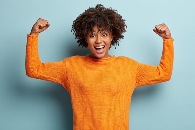 Gelukkig afro-amerikaanse vrouw met krullend haar, heft handen op en toont spieren, toont haar kracht, draagt oranje trui Gratis Foto