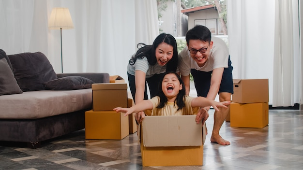 Gelukkig aziatisch jong gezin plezier lachen verhuizen naar nieuw huis. japanse ouders moeder en vader glimlachen helpende opgewekte meisje berijdende zitting in kartondoos. nieuw onroerend goed en verhuizing. Gratis Foto