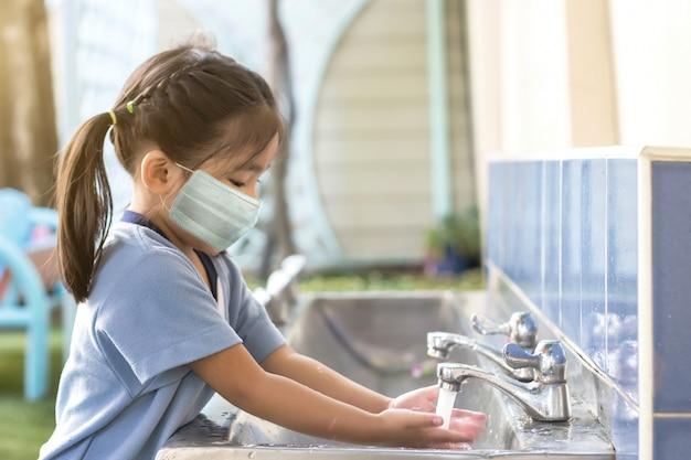 Gelukkig aziatisch kind dat hand wast na buiten spelen met masker wanneer terug naar school na coronavirus pandemie afname Premium Foto