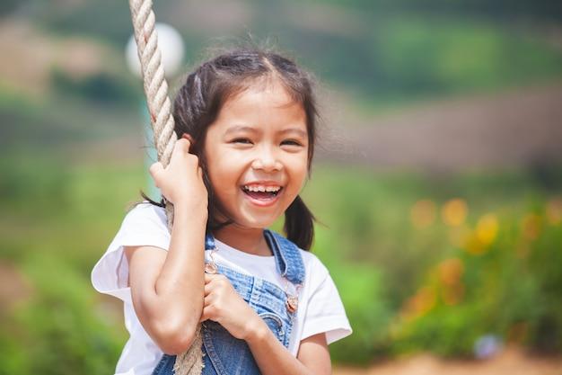 Gelukkig aziatisch kindmeisje die pret op houten schommeling in speelplaats hebben te spelen Premium Foto