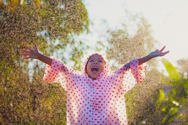 Gelukkig aziatisch kindmeisje die regenjas dragen die pret hebben om met de regen in het zonlicht te spelen Premium Foto