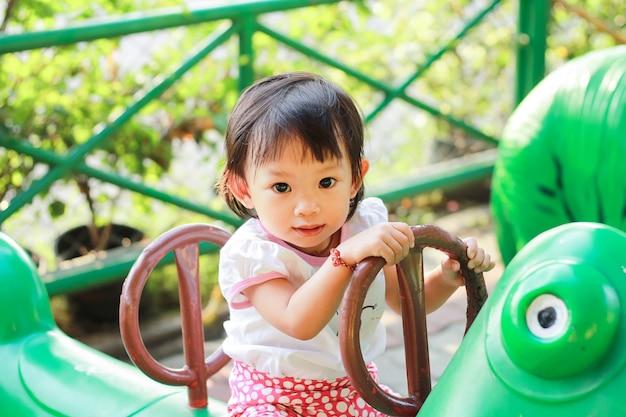 Gelukkig aziatisch kindmeisje het spelen speelgoed bij de speelplaats. ze glimlachte. Premium Foto