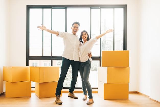 Gelukkig aziatisch paar bij het bewegen van dag naar nieuw huis Premium Foto