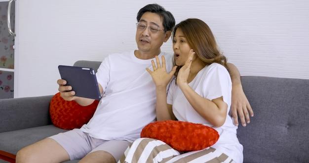 Gelukkig aziatisch paar die foto's samen in woonkamer nemen. Premium Foto