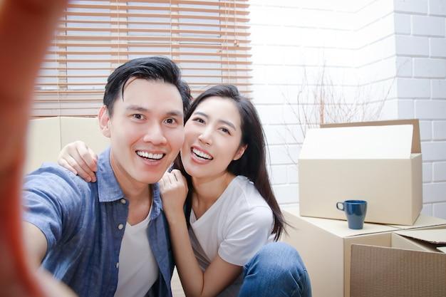 Gelukkig aziatisch paar verhuizen naar een nieuw huis neem een smartphone en maak een selfie. concept van het starten van een nieuw leven bouw een gezin. Premium Foto