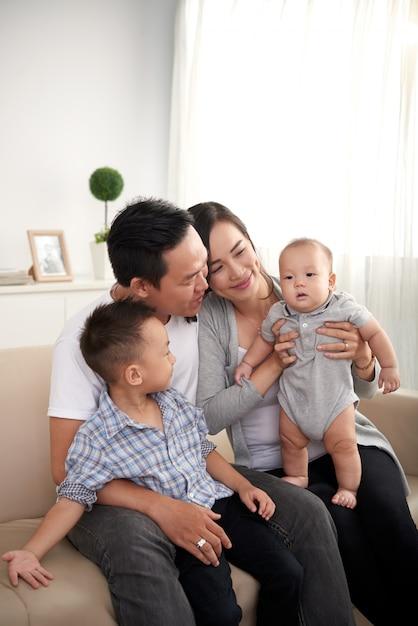 Gelukkig aziatische man, vrouw en twee kinderen thuis op de bank zitten Gratis Foto