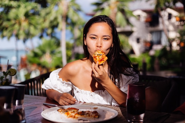 Gelukkig aziatische mooie vrouw hongerig met pizza op zonnige dag zonsondergang licht in openluchtrestaurant vrouw genieten van eten met plezier tijdens de lunch Gratis Foto