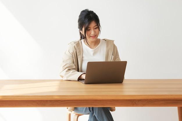 Gelukkig aziatische vrouw die vanuit huis werkt Gratis Foto
