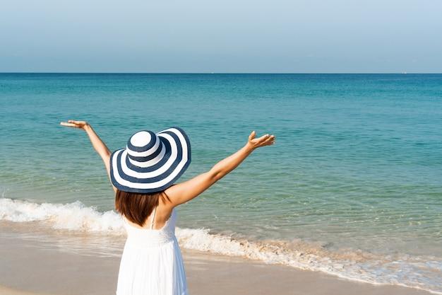 Gelukkig aziatische vrouw in witte jurk geniet op tropisch strand op vakantie. zomer op strand concept. Premium Foto