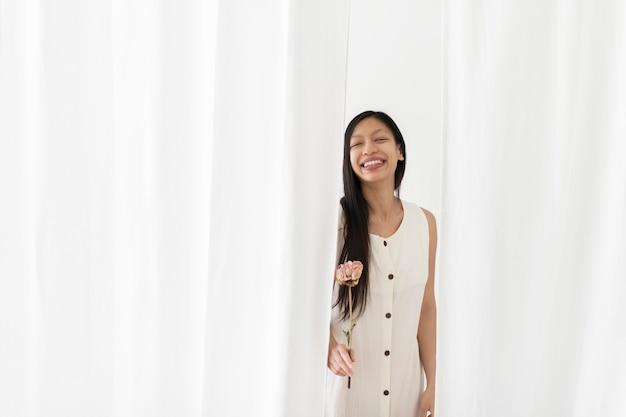 Gelukkig aziatische vrouw met een droge roze pioenroos bloem in een hand onder het witte gordijn Gratis Foto