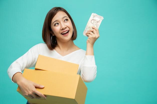 Gelukkig aziatische vrouw pakket pakket doos houden en vieren met geld bankbiljetten thaise baht geïsoleerd op groene achtergrond, levering koerier en lijndienst concept Premium Foto