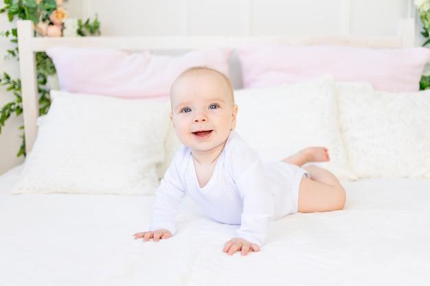Gelukkig babymeisje 6 maanden oud in een witte romper liggend op haar buik op een wit bed thuis Premium Foto