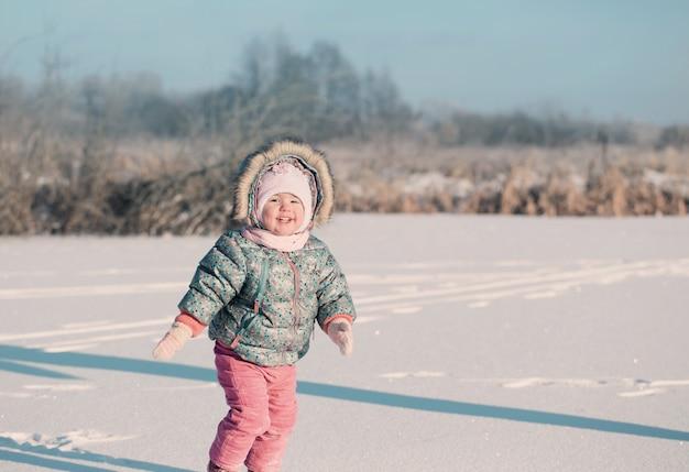 Gelukkig babymeisje op sneeuw Premium Foto