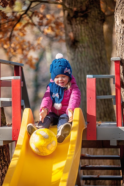 Gelukkig babymeisje van drie jaar in jasje op dia bij park Gratis Foto