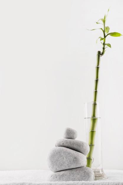 Gelukkig bamboe in vaas dichtbij de stapel kuuroordstenen op handdoek tegen witte achtergrond Gratis Foto