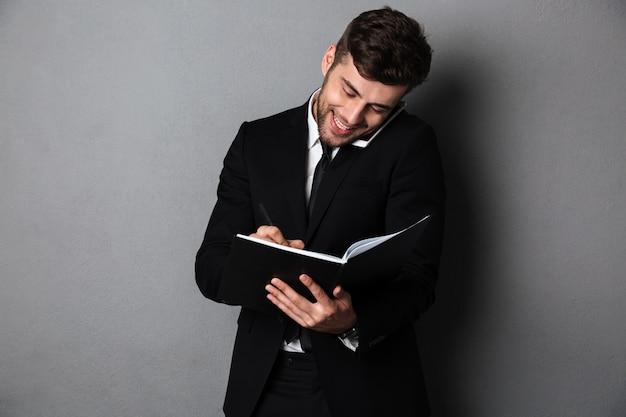 Gelukkig bebaarde man in zwart pak het maken van aantekeningen tijdens het praten op smartphone Gratis Foto