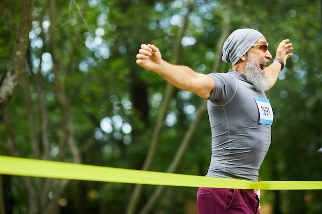 Gelukkig bebaarde senior man met pet en zonnebril winnen van de eerste plaats in de marathonrace, kopie ruimte Premium Foto
