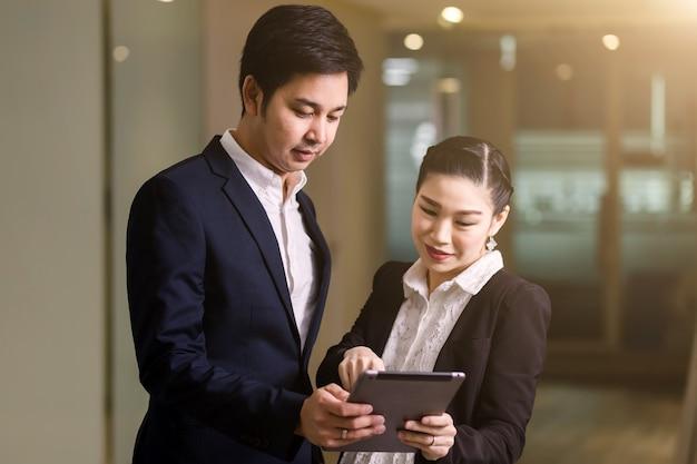 Gelukkig bedrijfspaar met tablet Premium Foto