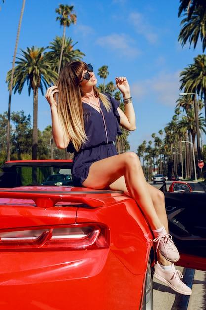 Gelukkig beïnvloedbaar meisje met opgeheven hand poseren op rode converteerbare auto op verbazingwekkende palmen en lucht in zonnig californië tijdens haar vakantie. Gratis Foto