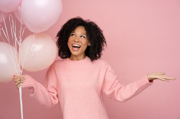 Gelukkig biracial vrouw met krullend haar met veel ballonnen Premium Foto