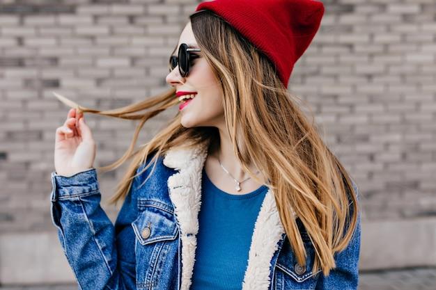 Gelukkig blanke vrouw met lichtbruin haar tijd buiten doorbrengen in koude lentedag. portret van schattig vrouwelijk model in rode hoed en zwarte bril genieten van wandeling door de stad. Gratis Foto