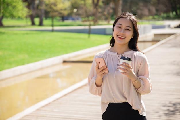 Gelukkig blij aziatisch meisje met smartphone en koffie wandelen Gratis Foto