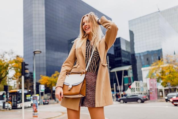 Gelukkig blond meisje in lente casual outfit buiten wandelen en genieten van vakantie in grote moderne stad. droeg een wollen beige jas en een gestripte blouse. stijlvolle accessoires. Gratis Foto