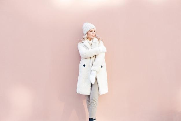 Gelukkig blondemeisje in witte de winterkleren die tegen een roze muur stellen. Premium Foto