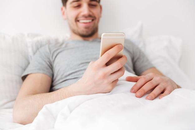 Gelukkig brunette man liggend op bed tijdens het gebruik van smartphone Premium Foto