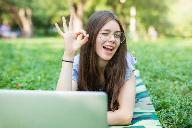 Gelukkig brunette vrouw in brillen liggend op gras in park met laptopcomputer en ok teken tonen Gratis Foto