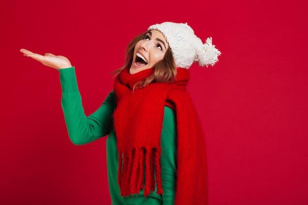 Gelukkig brunette vrouw in trui, grappige muts en sjaal Gratis Foto