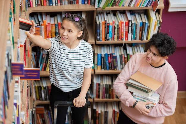 Gelukkig casual tiener die een van de boeken van haar favoriete auteur uit de grote boekenplank in de universiteitsbibliotheek neemt met een man in de buurt Premium Foto