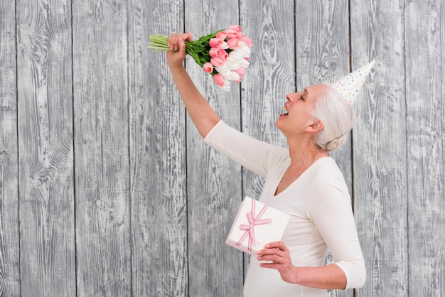 Gelukkig de tulpenboeket van de vrouwenholding en giftdoos voor grijze achtergrond Gratis Foto