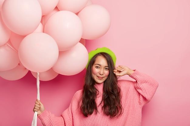 Gelukkig donkerharige oost-meisje houdt bos luchtballons, draagt groene baret en oversized trui Gratis Foto