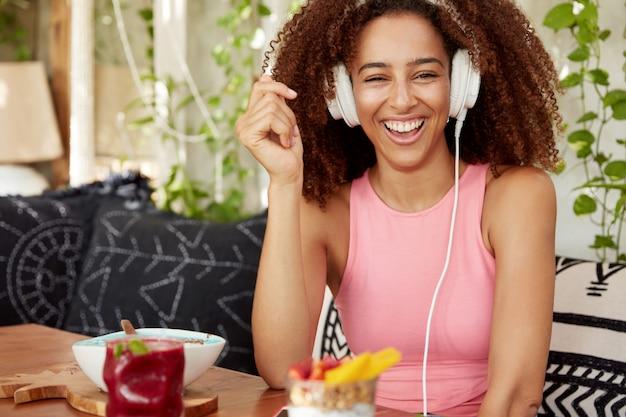 Gelukkig donkerhuidig vrouwelijk model met brede glimlach, lacht vreugdevol als anekdotes online in koptelefoons hoort, verbonden met moderne slimme telefoon, internetpost op website publiceert, rust in café. Gratis Foto