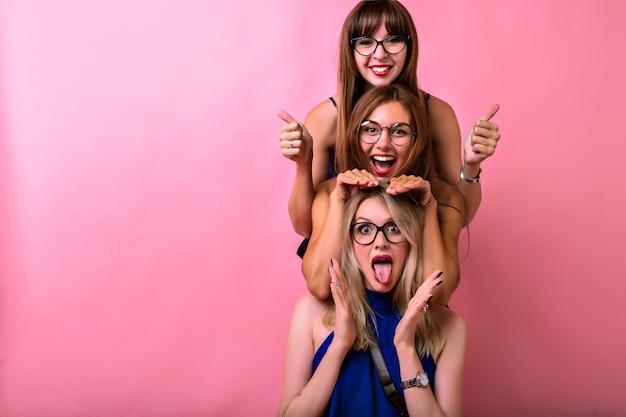 Gelukkig drie meisjes knuffels en samen plezier hebben, positieve gekke emoties, vriendschapsdoelen, heldere glazen, lichte kleding en roze ruimte. Gratis Foto
