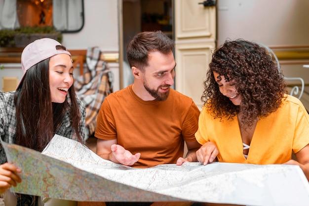 Gelukkig drie vrienden die een kaart bekijken Gratis Foto