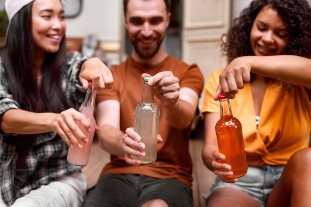 Gelukkig drie vrienden die hun drankjes openen Gratis Foto