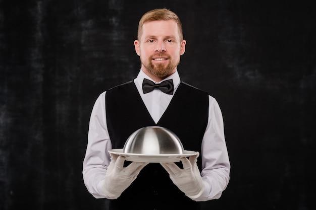 Gelukkig elegante ober van stijlvol restaurant in zwart vest en bowtie en wit overhemd en handschoenen met cloche Premium Foto