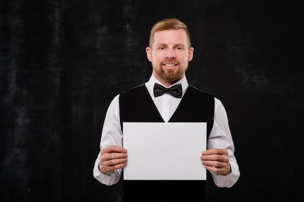 Gelukkig elegante ober van stijlvol restaurant in zwart vest en bowtie met blanco papier terwijl je voor de camera staat Premium Foto