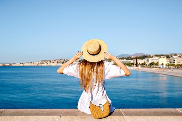 Gelukkig elegante vrouw die terug poseert, haar hand in de lucht steekt en geniet van een prachtig uitzicht in frankrijk Gratis Foto