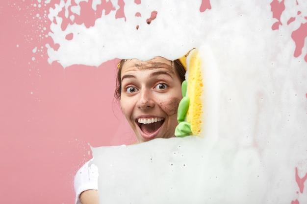 Gelukkig emotionele jonge vrouw met vuil op haar gezicht in opwinding kijken terwijl ze huishoudelijke taken doet, kamers in haar appartement schoonmaken, ramen wassen, chemische producten en doek gebruiken Gratis Foto