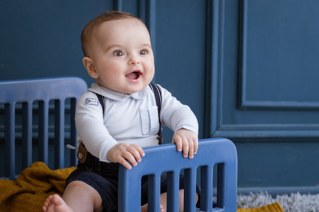 Gelukkig en glimlachend kind met gezellige outfits in de kamer. Gratis Foto