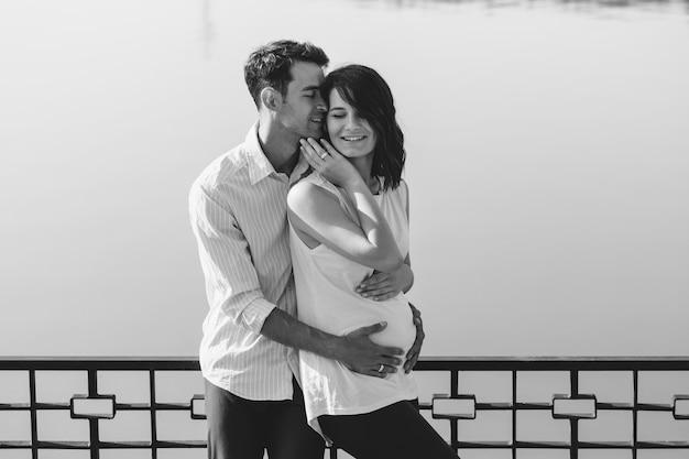 Gelukkig en jong zwanger paar die in aard bij het meer koesteren Gratis Foto