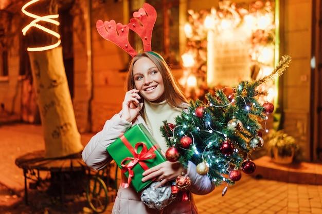 Gelukkig en mooi kaukasisch meisje dat een kerstboom houdt en aan de telefoon spreekt Premium Foto